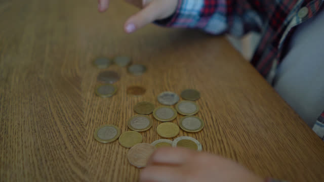 unrecognizable boy counting his coins on table - moneta video stock e b–roll