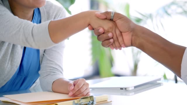 Unrecognizable business colleagues greet one another with a handshake