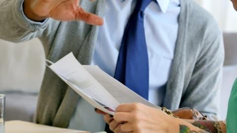 認識できないビジネス同僚議論財務書類 - paperwork点の映像素材/bロール