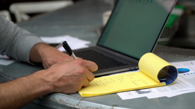 Unrecognizable business owner at his restaurant doing the books using a laptop