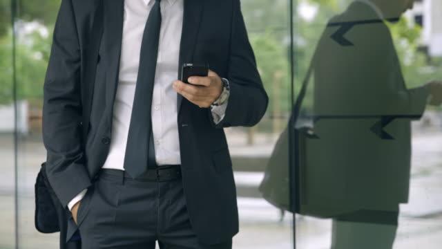 stockvideo's en b-roll-footage met slo mo onherkenbare zakenman die de tijd controleert en zijn smartphone buiten het kantoor gebruikt - alleen mid volwassen mannen