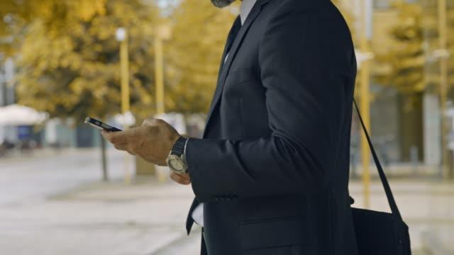 stockvideo's en b-roll-footage met slo mo onherkenbare zakenman die de tijd controleert en zijn smartphone buiten het kantoor gebruikt - mid volwassen mannen
