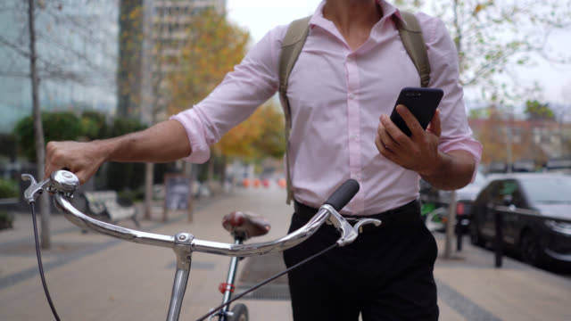 unrecognizable businessman commuting to work walking next to his bicycle while reading a text on smartphone - commuter stock videos & royalty-free footage