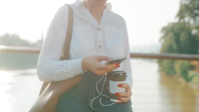 vidéos et rushes de femme d'affaires méconnaissable de sp utilisant un téléphone intelligent, prenez le café - chemise