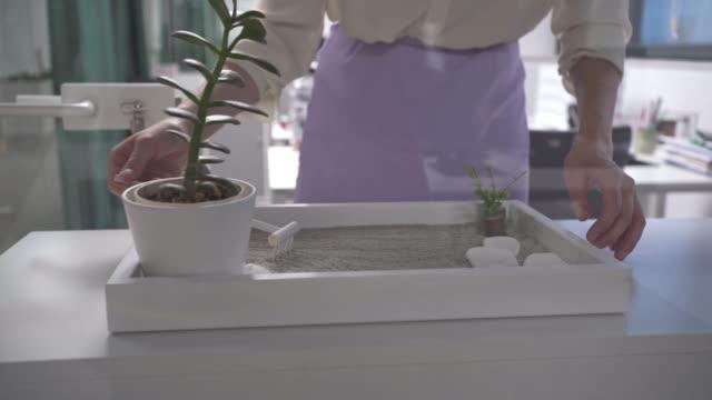 vidéos et rushes de femme d'affaires méconnaissable utilisant un jardin zen au travail - bien être