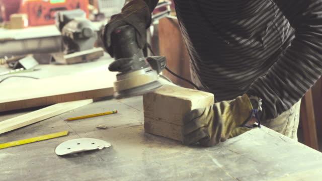 unrecognizable carpenter using sander on a piece of wood in carpentry workshop. - sander stock videos & royalty-free footage