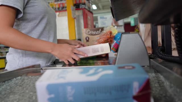 stockvideo's en b-roll-footage met niet-herkenbare kassier uitchecken voor klant scan producten - dairy product