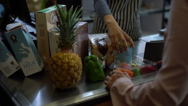 stockvideo's en b-roll-footage met onherkenbaar kassier scannen producten voor klant vertrekken bij een supermarkt - dairy product