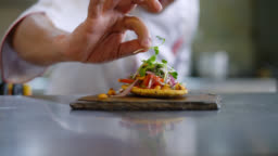 Unrecognizable chef decorating an appetizer on a stone plate