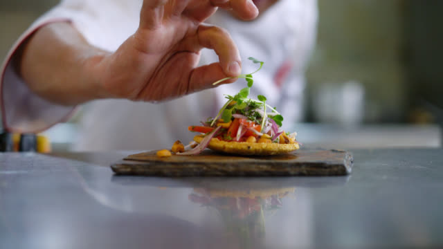unrecognizable chef decorating an appetizer on a stone plate - ristorante video stock e b–roll