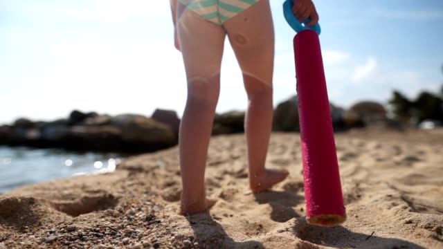 unrecognizable child walking on the beach carrying a squirt gun - sea squirt stock videos & royalty-free footage