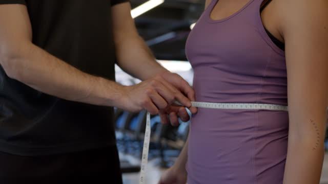 vídeos y material grabado en eventos de stock de entrenador irreconocible midiendo mujer en el gimnasio - medir