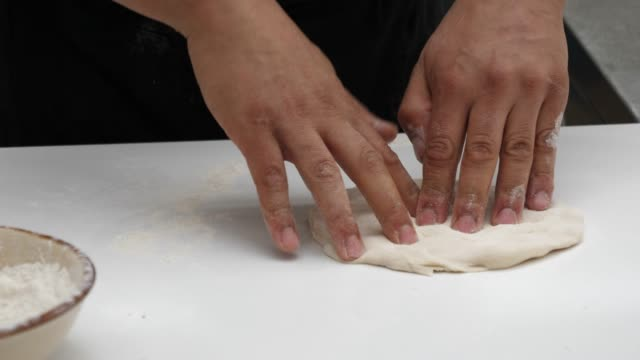 unrecognizable cook making a pizza kneading the dough and using a metallic rolling pin - italian food stock videos and b-roll footage