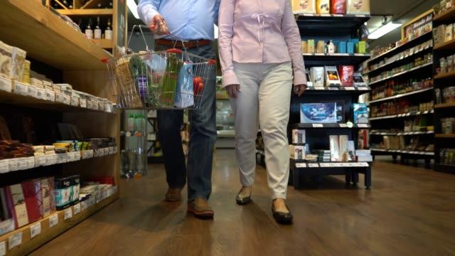 vídeos y material grabado en eventos de stock de pareja irreconocible en el supermercado compras - hombres maduros