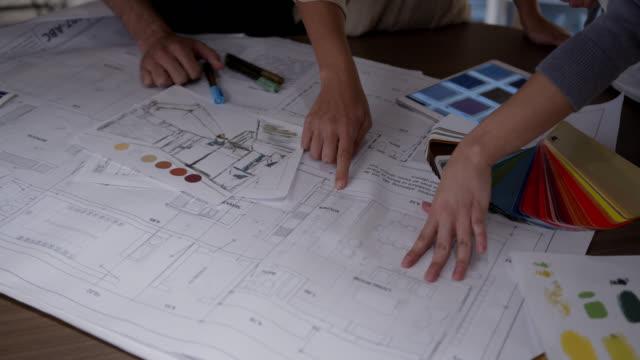 nicht erkennbare designer, die an einem projekt arbeiten, indem sie farben auswählen und dabei auf verschiedene skizzen und blaupausen zeigen - designer einrichtung stock-videos und b-roll-filmmaterial