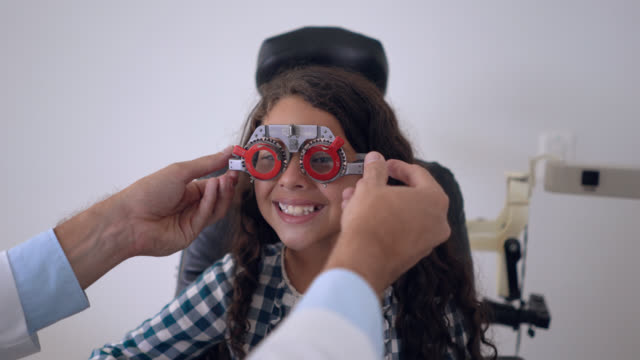 unrecognizable doctor putting on try out lens glasses to paediatrics patient while she smiles cheerfully at camera - optometrist stock videos & royalty-free footage
