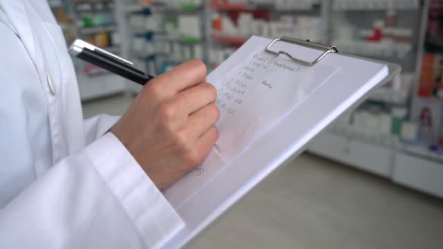 Unrecognizable doctor writing a medical prescription