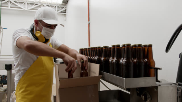 unrecognizable employee at a brewery factory packing bottles in carton box at the end of the production line - factory stock videos & royalty-free footage