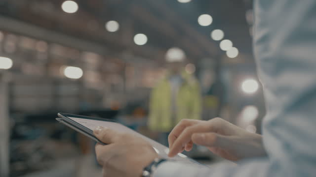 slo mo unrecognizable employee using a digital tablet in the factory - using digital tablet stock videos & royalty-free footage