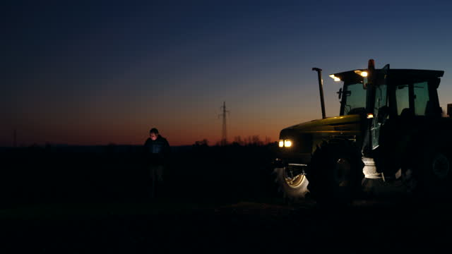 slo mo unrecognizable farmer walking back to his tractor on the field at night - 50 seconds or greater stock videos & royalty-free footage