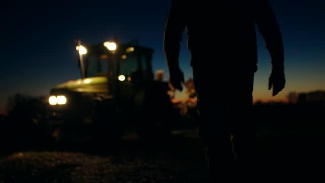 vídeos de stock e filmes b-roll de slo mo unrecognizable farmer walking to his tractor on the field at night - agricultor