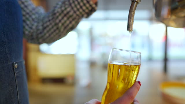 unrecognizable female bartender pouring beer into a glass - lager stock videos & royalty-free footage