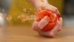 SLOW MOTION, MACRO: Unrecognizable female chef squeezing a ripe organic tomato.