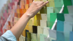 Unrecognizable female customer at a paint shop looking at color samples