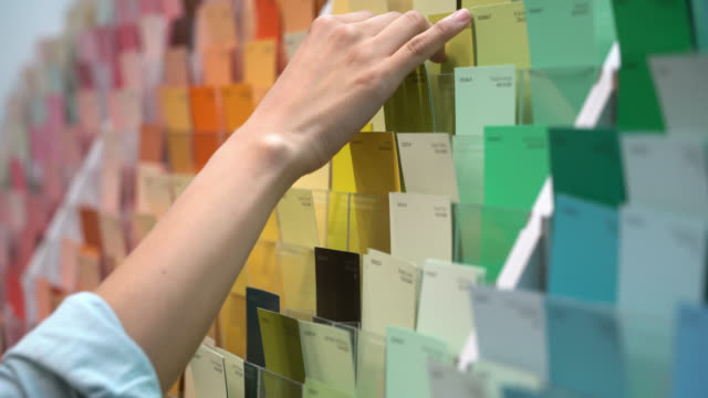unrecognizable female customer at a paint shop looking at color samples - renovation stock videos & royalty-free footage
