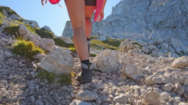 vidéos et rushes de randonneur féminin méconnaissable de la marchant sur un chemin de montagne - pied