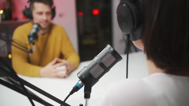 oigenkännlig kvinnlig värd som pratar med ung man i hennes radiopratshow - arbetsstudio bildbanksvideor och videomaterial från bakom kulisserna