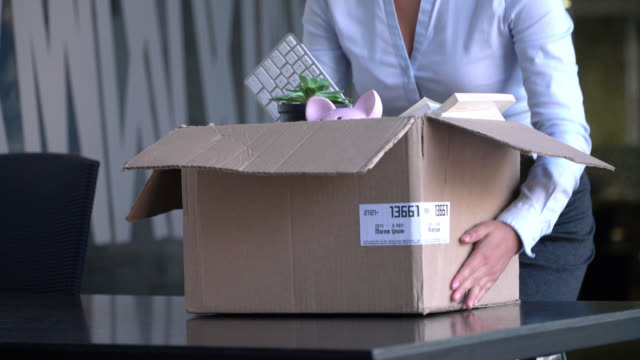 unrecognizable female new hire carrying a box to her office and unpacking it - new hire stock videos & royalty-free footage