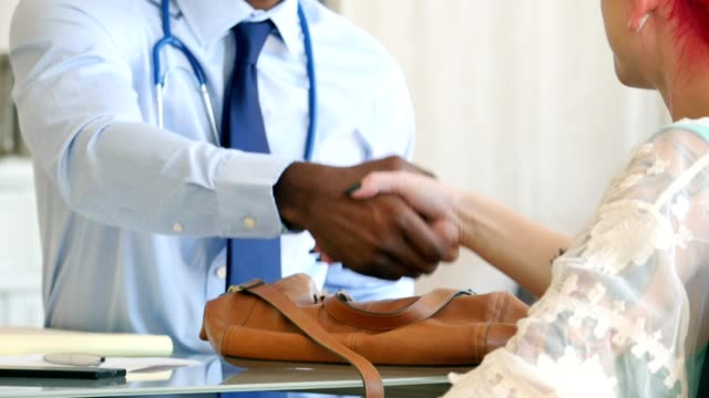 Unrecognizable female patient shakes hands with male doctor