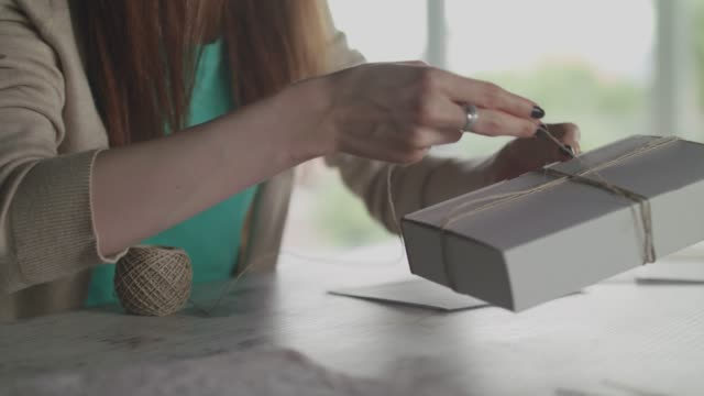unrecognizable female tying a string on a gift box she put together - altruismo video stock e b–roll