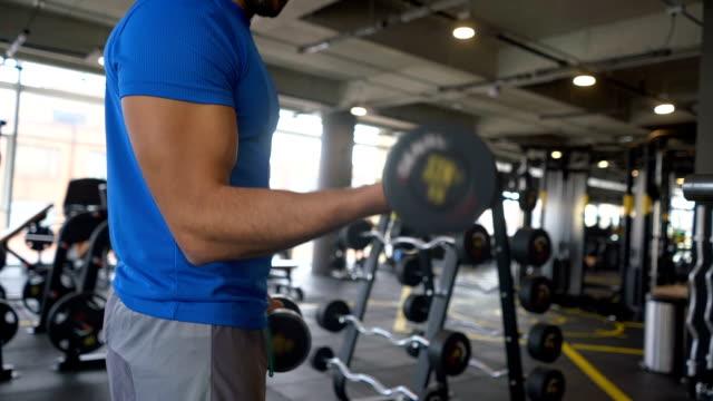 Hombre haciendo ejercicios de brazo levantar pesas ajuste irreconocible