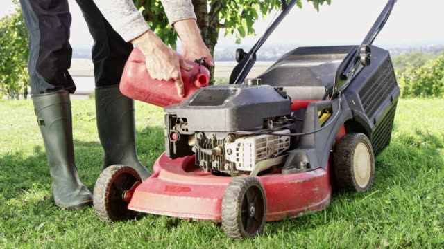 ds unrecognizable gardener refueling a lawn mower - refuelling stock videos & royalty-free footage