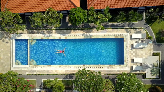 AERIAL TOP DOWN Unrecognizable girl in pink bikini enjoys swimming in empty pool
