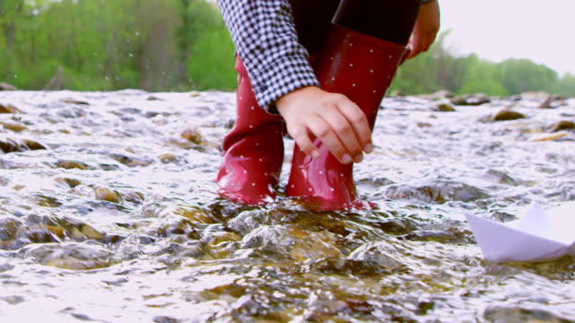 slo mo unrecognizable girl runs a paper boat over fast flowing stream - wet stock videos & royalty-free footage