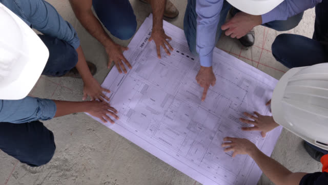 unrecognizable group of architects, engineers and blue collar workers looking at a blueprint while man points at different things - lavoro manuale video stock e b–roll