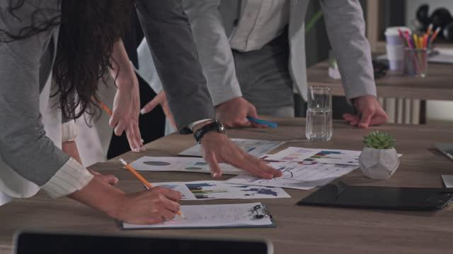 vídeos y material grabado en eventos de stock de grupo irreconocible de empresarios revisando la documentación durante una reunión - mesa negociadora