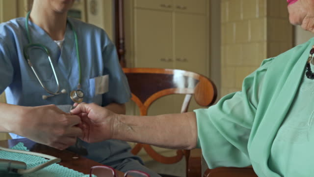Unrecognizable healthcare worker measuring blood pressure of an old woman at home.