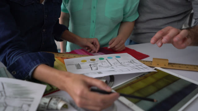 Unrecognizable interior designer and customers pointing at a design and different samples of textiles and colors on a tablet