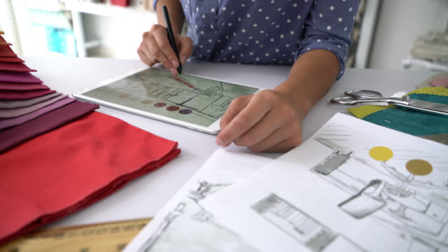 unrecognizable interior designer working on tablet trying out colors on a design with fabric samples on table - textile industry stock videos & royalty-free footage