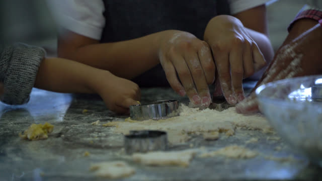 vídeos de stock e filmes b-roll de unrecognizable kids and adult baking christmas cookies at home - fazer doces
