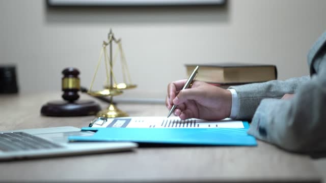 unrecognizable lawyer's hand works with papers and law books in courtroom or office. concept of justice and law, attorney or court judge - defendant stock videos & royalty-free footage