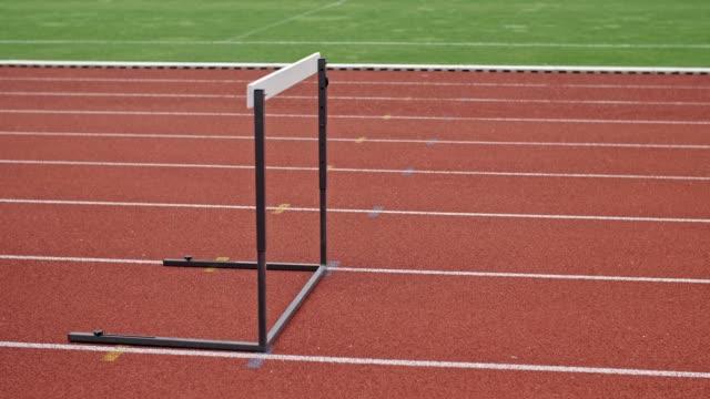 unrecognizable male athlete overcome obstacles on track field. - superare le avversità video stock e b–roll