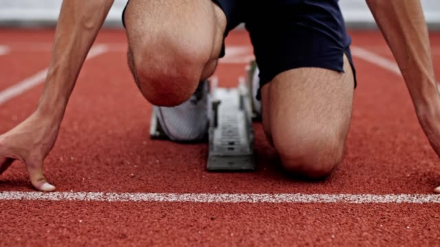 unrecognizable male athlete preparing at starting line. - pista di atletica leggera video stock e b–roll