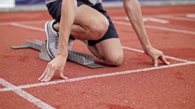 unrecognizable male athlete sprinter starting at sprinter block. - blocco di partenza per l'atletica video stock e b–roll