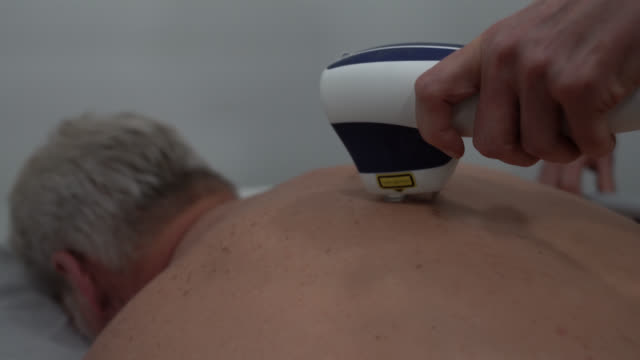 unrecognizable male customer getting a laser treatment on back at the spa - masseur stock videos & royalty-free footage