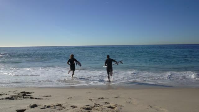oigenkännlig manliga vänner kör mot havet redo att surfa med sina styrelser - surfbräda bildbanksvideor och videomaterial från bakom kulisserna